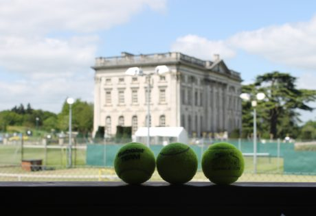 tennis balls with shot of the mansion