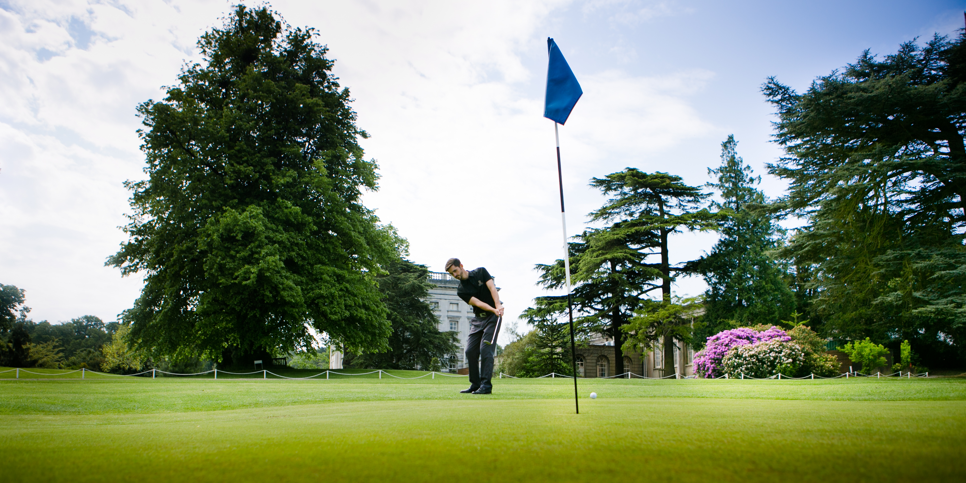 Man putting with flag in hole