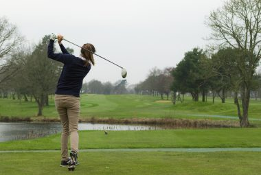 Woman taking tee shot